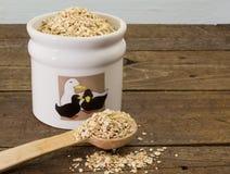 Pot démodé avec l'avoine roulée crue et la cuillère en bois Photographie stock
