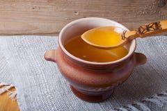 Pot d'argile avec le ghee et la cuillère sur la serviette de toile Toujours durée rustique images stock