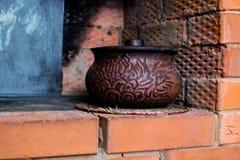 Pot d'argile de Brown dans le fourneau russe photo stock