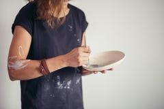Pot d'argile de peinture de femme avec le potier supérieur à l'atelier Photographie stock
