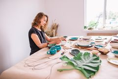 Pot d'argile de peinture de femme avec le potier supérieur à l'atelier Images libres de droits