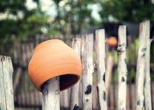 Pot d'argile sur la barrière en bois image stock