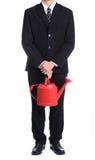 Pot d'arrosage rouge de prise d'homme d'affaires photos libres de droits
