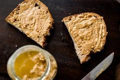 Pot de beurre d'arachide crémeux avec du pain et le couteau sur la surface en bois pour le petit déjeuner image stock