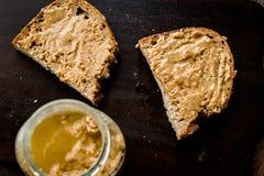 Pot de beurre d'arachide crémeux avec du pain sur la surface en bois pour le petit déjeuner photos libres de droits