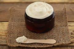 Pot de beurre de corps avec la cuillère en bois Image stock