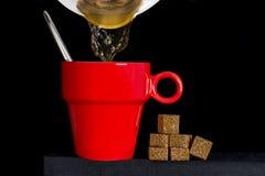 Pot de café remplissant tasse rouge photographie stock libre de droits