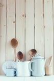 Pot de café, tasses d'émail et cuillères rustiques Photo stock