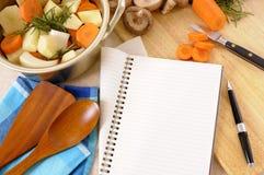 Pot de cocotte en terre avec les légumes et les herbes organiques sur le plan de travail de cuisine avec le livre de cuisine ou l Photo libre de droits