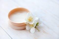 Pot de crème de beauté avec la fleur de jasmin sur la fin en bois blanche de table  Images stock
