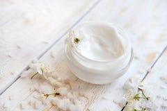 Pot de crème de beauté entouré par les fleurs et le sel de mer Photos libres de droits