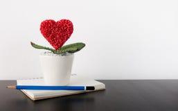Pot de fleur d'amour sur le journal intime de carnet Image libre de droits