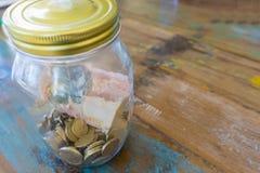Pot de l'épargne avec les pièces de monnaie et le billet de banque photographie stock libre de droits