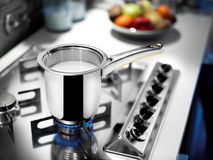 Pot de lait sur le cuiseur Photo stock