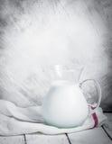 Pot de lait sur le fond rustique en bois Photo stock