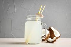 Pot de maçon avec l'eau de noix de coco et les écrous frais Images stock