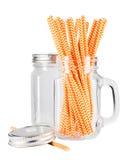 Pot de maçon en verre avec les pailles oranges Images stock