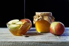 Pot de miel rustique et et de pommes sur la table en bois Nourriture traditionnelle de célébration pendant la nouvelle année juiv Images libres de droits