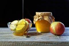 Pot de miel rustique et et de pommes sur la table en bois Nourriture traditionnelle de célébration pendant la nouvelle année juiv Photographie stock