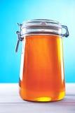Pot de miel sur un fond bleu Photographie stock libre de droits