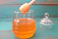 Pot de miel sur un fond en bois de turquoise Images libres de droits