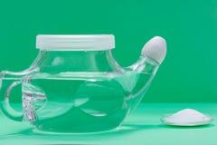 Pot de Neti avec l'astuce de confort et la pile molles du bicarbonate de soude et du chlorure de sodium salins sur le fond vert L images stock