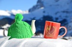 Pot de thé dans la capsule tricotée et la tasse rouge Images stock