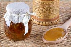 Pot deux de miel et de cuillère avec du miel sur le fond rustique Photos stock