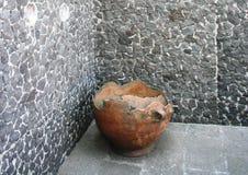 POT di argilla antico contro una parete di pietra fotografia stock libera da diritti