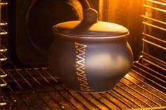 Pot en céramique fermé en four électrique lumineux Image stock
