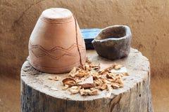 Pot en céramique inversé se tenant sur un tronçon d'arbre avec les champignons secs photos stock