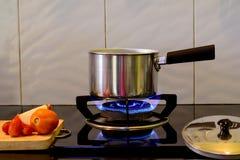 Pot en métal sur la cuisinière à gaz de flamme pour la soupe à eau bouillante, image stock