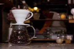 Pot en verre avec des grains de café sur une table en bois Photo stock