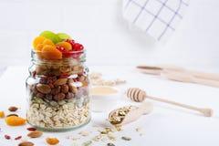 Pot en verre avec des ingrédients pour faire cuire la granola sur le fond blanc Flocons, miel, écrous, fruits secs et graines d'a photographie stock