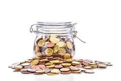 Pot en verre avec des pièces de monnaie Photographie stock libre de droits