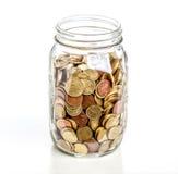 Pot en verre avec des pièces de monnaie Photos stock