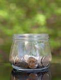 Pot en verre avec des pièces de monnaie sur le fond vert Images libres de droits