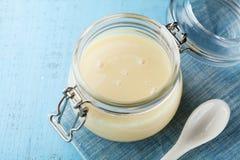 Pot en verre avec du lait condensé ou le lait concentré non sucré sur la table rustique bleue Images libres de droits