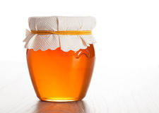 Pot en verre avec du miel d'isolement Photographie stock
