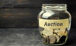 """Pot en verre avec l'argent et l'inscription """"vente aux enchères """" Ventes publiques, propriété des entreprises, négociant Organisa image stock"""