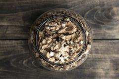 Pot en verre avec la bande pleine des noix criquées Photo stock