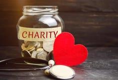 Pot en verre avec la charité de mots et le coeur Le concept d'accumuler l'argent pour des donations économie Aide médicale social images stock