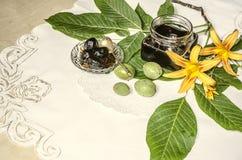 Pot en verre avec la confiture d'écrou près des noix vertes avec des feuilles et des lis oranges Photo libre de droits
