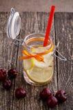 Pot en verre avec le citron, les cerises et la glace Images stock