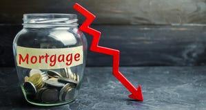"""Pot en verre avec les pièces de monnaie et l'inscription """"hypothèque """"et vers le bas flèche Intérêt réduit pour l'hypothèque Bas  photos stock"""