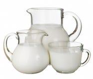 Pot en verre avec une tasse délicieuse de lait d'isolement Photo stock