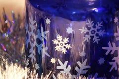 Pot en verre bleu avec les flocons de neige blancs Photo stock
