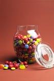 Pot en verre complètement des sucettes et de la sucrerie colorées lumineuses avec le couvercle ouvert - verticale avec l'espace de Image libre de droits