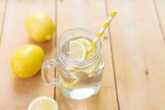 Pot en verre de maçon avec l'eau, les citrons frais et les pailles sur la table en bois Été chaud frais images libres de droits
