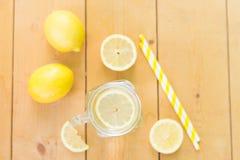 Pot en verre de maçon avec l'eau, les citrons frais et les pailles sur la table en bois Configuration plate Préparez pour le cock photographie stock